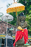 Statues and ceremonial umbrella decorations at a temple near Tabanan in Bali, Indonesia