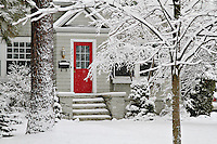 A red door in a white winter wonderland.