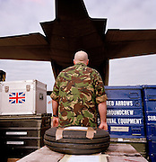 Chief Technician Kerry Griffiths is a with the 'Red Arrows', Britain's Royal Air Force aerobatic team, the elite 'Red Arrows', Britain's prestigious Royal Air Force aerobatic team. In camouflaged military green jacket, large forearms and rolled-up sleeves, he oversees the loading of spares and personal effects into a C-130 Hercules aircraft before the two-day journey from RAF Scampton to RAF Akrotiri in Cyprus. Surrounded by heavy-duty flight-spares, survival equipment boxes and a tyre for a Hawk jet aircraft, the Hercules looms large in the overcast sky. The team complete their winter training schedule in Cyprus. The Red Arrows pilots fly their own jet aircraft to air shows but when requiring the support of ground crew  they borrow a transporter to fly behind the main airborne squadron. 10 tons of spares and personal effects are shipped for a six-week stay.
