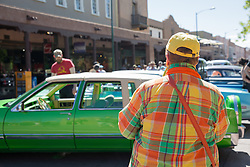 back of a woman in a colorful shirt looking a colorful car in Santa Fe, NM