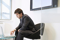 Tired Businessman Using Laptop in waiting room