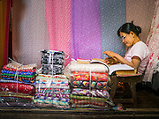 14 JUNE 2013 -  PATHEIN, AYEYARWADY, MYANMAR: A fabric vendor in the market in Pathein. Pathein, sometimes also called Bassein, is a port city and the capital of the Ayeyarwady Region, Burma. It lies on the Pathein River (Bassein), which is a western branch of the Irrawaddy River. It's the fourth largest city in Myanmar (Burma) about 190 km west of Yangon.   PHOTO BY JACK KURTZ