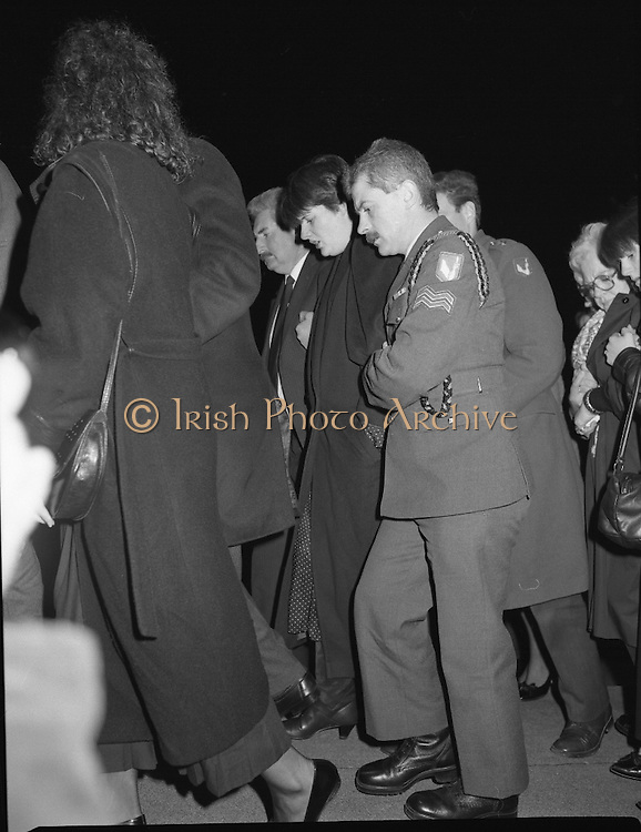 Irish Soldiers Bodies Returned From Lebanon. (R99)..1989..24.03.1989..03.24.1989..24th March 1989..While serving on the peacekeeping mission with the UN three Irish soldiers lost their lives when the vehicle they were in struck a land mine. The mine had ben planted by a Hezbollah Group who were targeting the Israeli military. The Soldiers; Corp Fintan Heneghan, Pte Mannix Armstrong and Pte Thomas Walshe were serving with C Company, 64th Infantry Batallion in Brashit, Sth Lebanon...Image shows Mrs Armstrong,widow of Pte Mannix Armstrong being escorted by military personnel on her arrival at the mortuary in Dublin Airport.