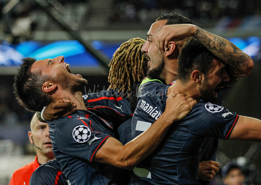 Olympiacos' Kostas Mitrogiou (C) celebrates with team mates Andreas Samaris (L) and Giannis Maniatis after scoring during the UEFA Champions League Group C soccer match between RSC Anderlecht and Olympiacos at Constant Vande Stock Stadium in Brussels, Belgium, 2 October 2013.