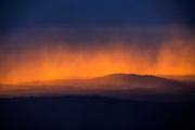 Heavy rain and hail streak across the golden sky over Hogwallow Flats at daybreak in Shenandoah National Park, Virginia.