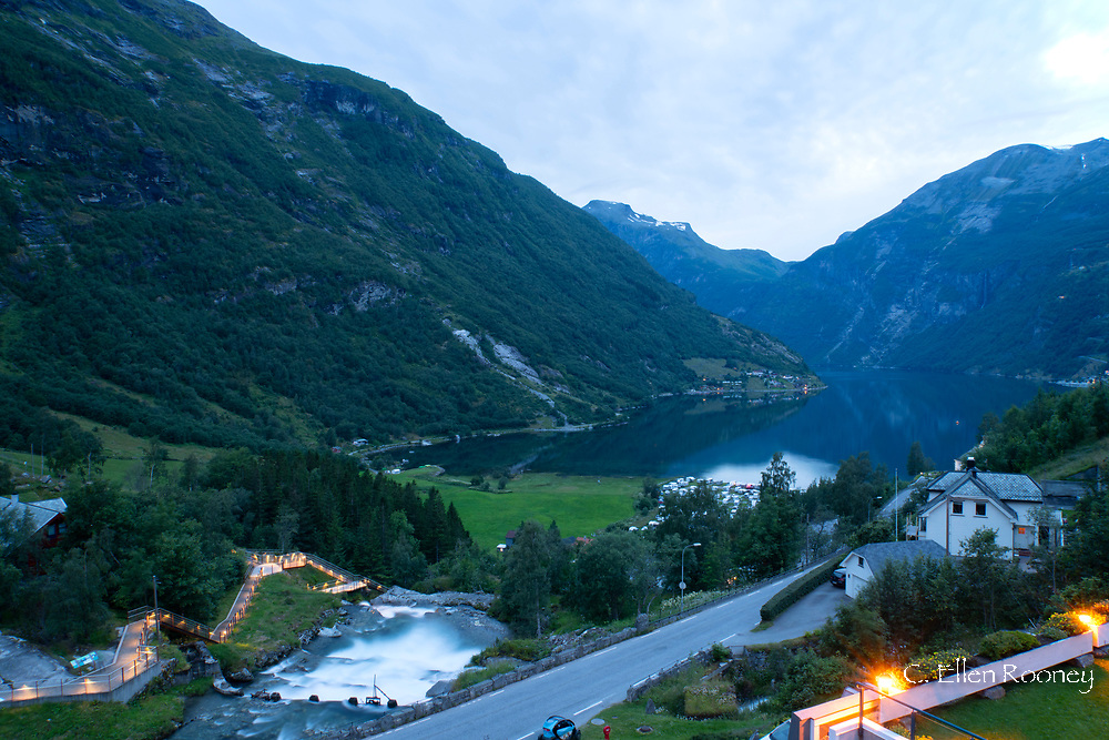 An aerial view of Gieranger Fjord and a waterfall and walkway in Geiranger at dusk.  Vestlandet, Norway