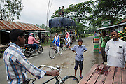A street seen in a one street village that is surrounded by enclaves. For residents of the enclaves in this area this town is where they come to buy basic necessities. In theory until the enclaves were disbanded they were illegally crossing an international border, leaving Indian territory for Bangladesh.<br /> <br /> On July 31st 2015 the enclaves that formed one of the world's most complicated borders were officially absorbed in to the countries that surrounded them in a land-mark land swap between India and Bangladesh. The people that lived in them will finally receive citizenship.<br /> <br /> Enclaves are small pockets of sovereign land completely surrounded by another sovereign nation. Approximately 160 enclaves, known as chitmahals, exist on either side of the India-Bangladesh border. For 68 years the 50,000 plus inhabitants of these enclaves have lived a difficult existence, stranded from their home nation and ignored by the country that surrounds them. <br /> <br /> In theory even leaving their enclaves is illegally crossing an international border and for decades it has been very difficult for them to receive even the most basic of rights whether education or health. Even the police have no jurisdiction in the enclaves leaving them essentially lawless.