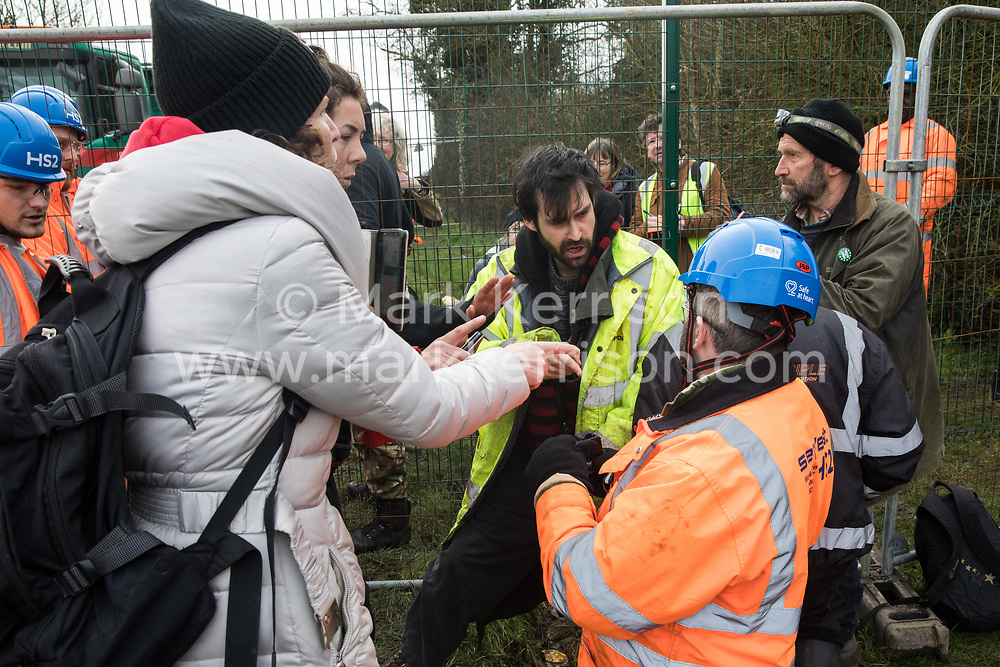 Harefield, UK. 8 February, 2020. HS2 engineers try to prevent environmental activists from Save the Colne Valley, Stop HS2 and Extinction Rebellion from accessing an area of Harvil Road fenced off in order to carry out tree felling works for the high-speed rail project. The activists were successful in gaining entry and preventing any of the scheduled tree felling by HS2 and after an intervention by a police officer all tree felling and strimming work has now been cancelled for the weekend.