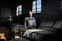 """SOVERIA MANNELLI, ITALY - 17 NOVEMBER 2016: Emilio Salvatore Leo (41), entrepreneur and heir of the woolen mill and historic family business Lanificio Leo, poses for a portrait by an old warping mill in Soveria Mannelli, Italy, on November 17th 2016.<br /> <br /> Lanificio Leo was the first and last machine-operated woolen mill of Calabria, founded in 1873, it employed 50 people until the 1970s, when national policies to develop Italy's South cut out small businesses and encouraged larger productions or employment in the public administration.<br /> <br /> The woolen mill was on stand-by for about two decades, until Emilio Salvatore Leo, 41, started inviting international designers and artists to summer residencies in Soveria Mannelli. With their inspiration, he tried to envision a future for his mill and his town that was not of a museum of the past,<br /> Over the years, Mr. Leo transformed his family's industrial converter of Calabrian wool into a brand that makes design products for home and wear. His century old machines now weave wool from Australia or New Zealand, cashmere from Nepal and cotton from Egypt or South America. He calls it a """"start-up on scrap metals,"""" referring to the dozens of different looms that his family acquired over the years.<br /> <br /> Soveria Mannelli is a mountain-top village in the southern region of Calabria that counts 3,070 inhabitants. The town was a strategic outpost until the 1970s, when the main artery road from Naples area to Italy's south-western tip, Reggio Calabria went through the town. But once the government started building a motorway miles away, it was cut out from the fastest communications and from the most ambitious plans to develop Italy's South. Instead of despairing, residents benefited of the geographical disadvantage to keep away the mafia infiltrations, and started creating solid businesses thanks to its administrative stability, its forward-thinking mayors and a vibrant entrepreneurship numbering a national"""