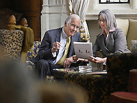 Business man and woman sitting indoors looking at documents