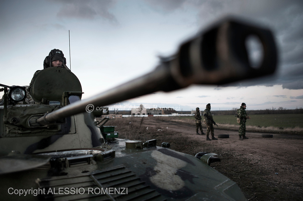 Ukraine, Myrne: An Ukrainian soldier is seen on a BMP Infantry Fighting Veicle as his comrades stand guard at the entrance of a temporary military camp set in the countryside of Myrne, an Ukrainian village located some 40 Km from the border with Russia on March 19, 2014. Ukrainian troops, armoured vehicles and tanks have been seen on their way to the eastern border with Russia. During the journey al least two convoys have been stopped by pro Russia protesters that prevented them to reach the border zone. ALESSIO ROMENZI