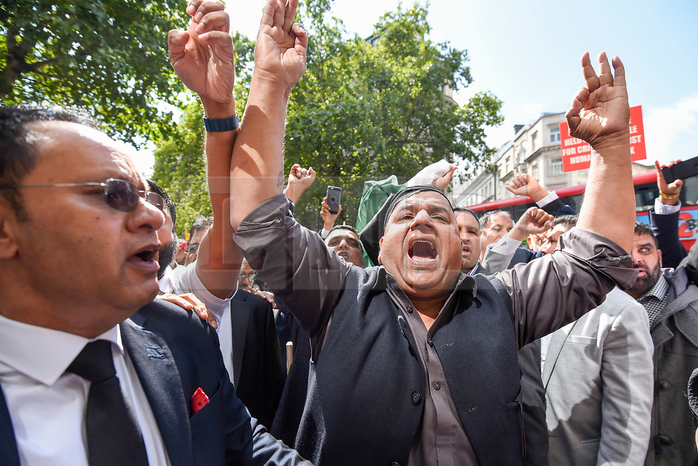 © Licensed to London News Pictures. 15/08/2019. LONDON, UK.  Men chant as thousands of protesters, many waving Pakistani and Kashmiri flags, gather outside the Indian High Commission in Aldwych, on what they are calling Black Day, to stand in solidarity with the people of Kashmir.  Indian Prime Minister Narendra Modi delivered an Independence Day speech highlighting his decision to remove the special rights of Kashmir as an autonomous region.  Photo credit: Stephen Chung/LNP