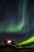 The aurora borealis dances over a boat on Great Slave Lake in Yellowknife, NWT.