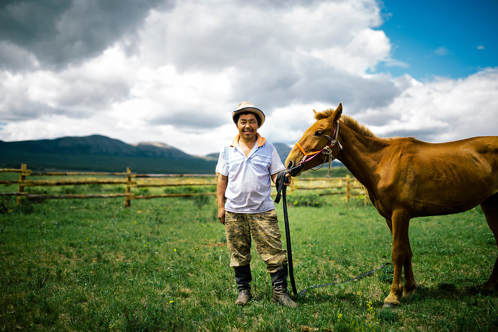 A Tsaatan man poses for a portrait with his horse in northern Mongolia.