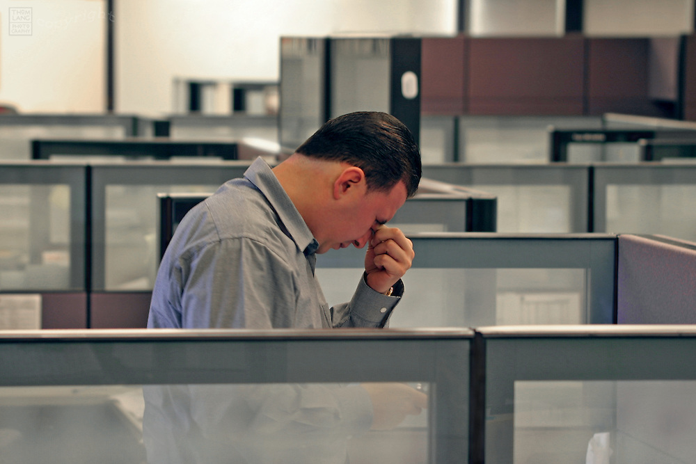 A businessman standing in an office cubilcle squeezes the bridge of his nose.