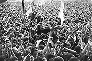 Concert crowd scene, with flags, two people on shoulders, UK, 1980's