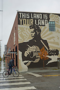 A bicyclist rides past a mural of Woody Guthrie that is painted on the side of the Woody Guthrie Center in the Brady District on Friday, October 18, 2013, in Tulsa, Oklahoma. <br /> <br /> http://www.thebradyartsdistrict.com/<br /> http://woodyguthriecenter.org/