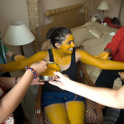 haldi (turmeric) paste is applied to the bride by her female relatives and friends a day before the wedding as a part of the Mehendi ceremony,