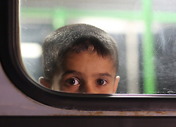 © London News Pictures. A young migrant boy is seen at the window of a bus close to the Hungarian and Serbian border town of Roszke, Hungary, September 8 2015. The UN's humanitarian agencies are on the verge of bankruptcy and unable to meet the basic needs of millions of people because of the size of the refugee crisis in the Middle East, Africa and Europe, senior figures within the UN have told the media.   Picture by Paul Hackett /LNP