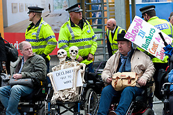 © Licensed to London News Pictures. 05/10/2015. Manchester, UK. Disabled activist stage a protest 'IDS Murderer' at the Tory venue. A week of pro-peace, anti-austerity, anti-war, anti-Tory, protests dubbed 'Take Back Manchester' has been  organised by The People's Assembly and timed to coincide with the Conservative Party Conference in Manchester on 4th - 7th Oct 2015. Over 40 events are planned, including a speech by new Labour leader Jeremy Corbyn timed to compete with closing speech of Tory leader David Cameron. Photo credit: Graham M. Lawrence/LNP