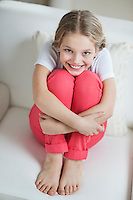 Portrait of a happy young girl sitting on sofa