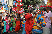 Turbaned man with a blue horse costume and men wearing tall headdresses with paper flowers, in the parade celebrating the festival of Ganesh Chaturthi, marking the birth of the Hindu god Ganesha, on the streets of the La Chapelle area of the 18th arrondissement of Paris, France, on Sunday 1st September 2019. The annual religious festivities and parade take place near the Ganesha Temple of Paris, or Sri Manicka Vinayakar Alayam Temple, the largest Hindu temple in France. Ganesha is the elephant-headed Hindu God of Beginnings, son of Shiva and Parvati, who represents love and knowledge. Picture by Manuel Cohen