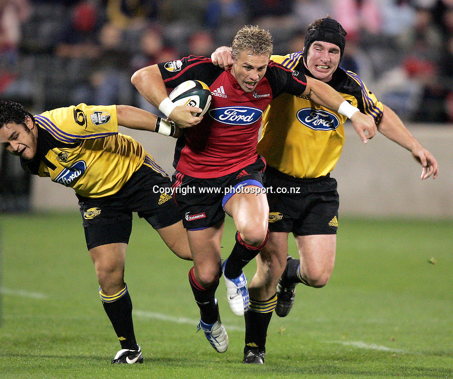 20/5/2005. Crusaders Justin Marshall breaks through the tackles of Piri Weepu(L)and Andrew Hore during the Super 12 semi final clash against the Hurricanes at Jade Stadium in Christchurch on Friday night. Photo: PHOTOSPORT