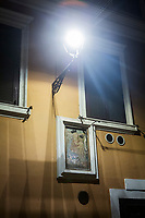 ROME, ITALY - 20 MARCH 2017: An image of the Virgin in a frame attached to a wall, with above it was a bare LED street lamp with its glass panes removed, is seen here in the Monti neighborhood in Rome, Italy, on March 20th 2017.<br /> <br /> Rome is undergoing a city-wide plan to change its public illumination from the current yellow sodium street lights CK to white LED lamps. In making the change, Rome joins a long line of cities around the world that have switched to the cheaper, and more environmentally friendly LED lighting, and it is not the first city where that change has come at the price of protest.<br /> <br /> Since July, some 100,000 led lights have already been installed, just over half the number that will be substituted in the 53 million euro changeover that is expected to save the city millions of euros in electrical bills. But when Rome's municipal electrical utility ACEA began to substitute the lamps in Rome's historic center, residents began to take note.