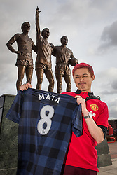 © Licensed to London News Pictures . 27/01/2014 . Manchester , UK . HUNG-JUI LIN , (27, tourist from Taiwan) poses with his new shirt in front of the United Trilogy statue . Fans with new MATA 8 shirts in front of Old Trafford Football Ground as it's announced that Spaniard Juan Mata ( Juan Manuel Mata García ) has signed for Manchester United  . Photo credit : Joel Goodman/LNP