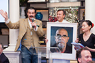 "Chef Daniel Boulud holds a self-portrait of Chuck Close as it is auctioned by Nicholas Lowry of Swann Auction Galleries at ""Burgundy, Black Truffles, and Denim,"" a charity dinner at Restaurant DANIEL to benefit Citymeals-on-Wheels."