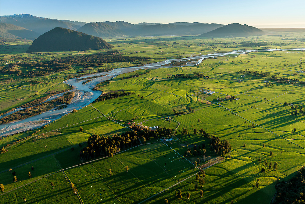 The Kokatahi River winds through lush farmland to the Tasman Sea, Westland, New Zealand.