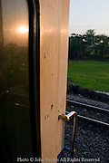 The setting sun is reflecting on a passenger train car passing rural farmland on a railroad track in Ayuttaya Province, Thailand.