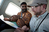 Kumi Naidoo, executive director of Greenpeace International (wearing yellow batik shirt), accompanied by Rolf Skar (senior forest campaigner of Greenpeace Forest Network), flies in a plane over Southern Sumatra province to witness first hand the beauty of the forest, and the encroaching destruction of it., in southern Sumatra province, Indonesia, Saturday 16th October 2010. The plantations for paper are owned by Asia Pulp and paper, a subsidiary of Sinar Mas.
