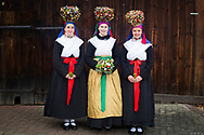 Lena, member of the Trachtengruppe Glasofen, is wearing a traditional bridal costume in Glasofen, Lower Franconia in Germany on March 4th, 2017.<br /> Theresa (left) and Melanie are wearing the traditional bridesmaids costumes.<br /> <br /> The bridal crown and necklace are original and from 1860 and 1850. After the WWII, the association was formed and to preserve the traditional costumes, the members crafted original copies.<br /> Glasofen is part of the Wertheim Shire, an evangelical area surrounded by catholic Hinterland.<br /> <br /> This is part of the series about Traditional Wedding Gowns from different regions of Germany, worn by young members of local dance groups and cultural associations that exist to preserve and celebrate the cultural heritage. The portraiture series is a depiction of an old era with different social values and religious beliefs in an antiquated civil society with very few of those dresses left.