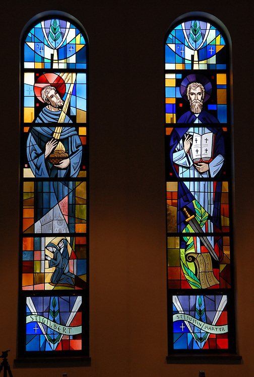 Two stained glass panels inside Our Lady Queen of Peace Church in Milwaukee depict St. Gilbert and St. Justin. (Photo by Sam Lucero)