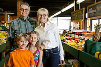 Portrait of a senior couple with grandchildren in farmer's market