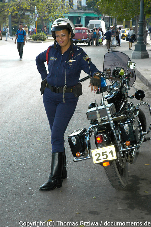 Charmante kubanische Polizistin mit ihrem Motorrad auf Streife in Havanna