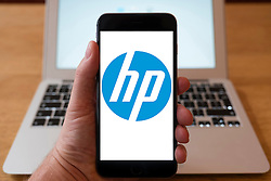 Using iPhone smartphone to display logo of HP, Hewlett Packard , American multinational information technology company