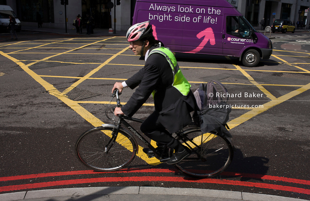 Cyclist turns a corner past a yellow box junction grid in a City of London street.