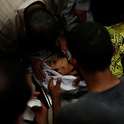 Palestinians mourn in a mosque the dead body of Ahmed, 14, who witnesses said was killed in an Israeli airstrike in Deir Al-Balah town in Central Gaza Strip.