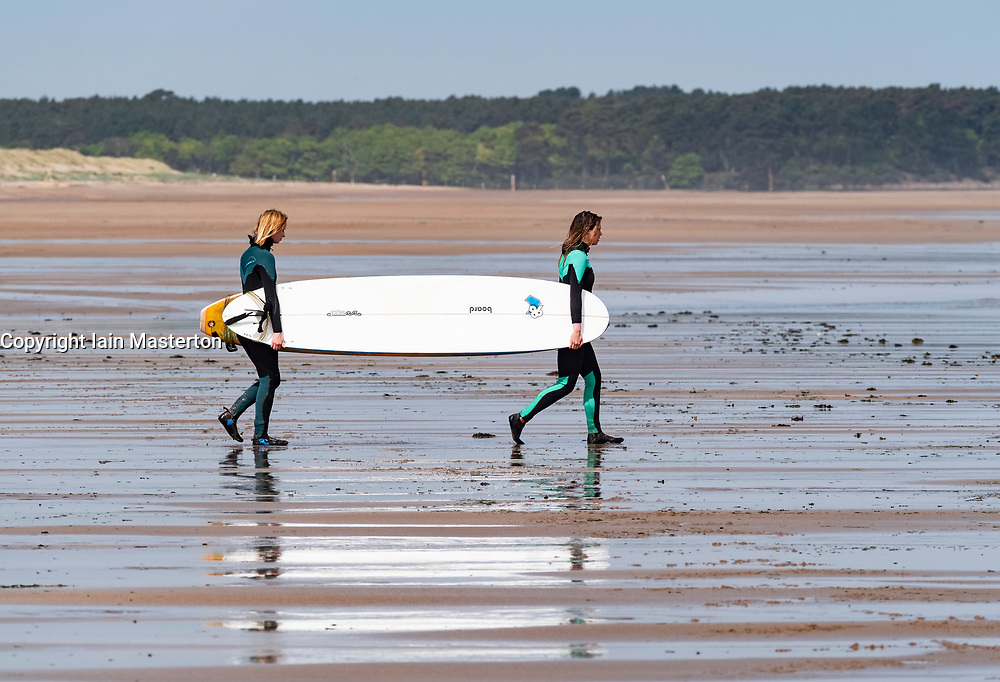 Two female surfers carry surfboards to sea at Belhaven Beach, East Lothian, Scotland, United Kingdom