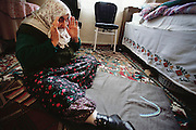 Ermine Çinar, 78, a Muslim, prays five times a day (at home, on the floor of the bedroom where her husband is resting), Golden Horn (or Haliç) area, Istanbul, Turkey.