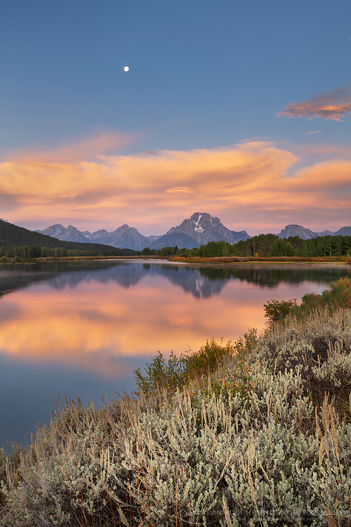 Full moon, orange clouds, and Mount Moran reflected in still waters of the Snake River at Oxbow Bend at sunrise, Grand Teton National Park Wyoming