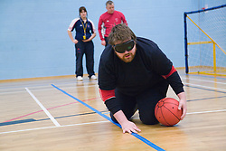 Team player getting into position by feeling tactile markings before throwing the ball during a Goalball game; a threeaside game developed for the visually impaired and played on a volleyball court,  A specially adapted ball containing an internal bell is used,
