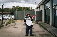 "TARANTO, ITALY - 22 FEBRUARY 2018: Raffaella Loperfido (46), a union activist distributing flyers, waits for employees of the ILVA steel mill at the exit to tell them not to vote in the upcoming Italian General Elections, in Taranto, Italy, on February 22nd 2018.<br /> <br /> The banner on the left says: ""No health, no job? No vote"".<br /> <br /> Taranto, a  formerly lovely town on the Ionian Sea has for the last several decades been dominated by the ILVA steel mill, the largest steel plant in Europe. It was built by the government in the 1960s as a means of delivering jobs to the economically depressed south, but has been implicated for a cancer as dioxin and mercury have seeped into local groundwater, tainting the food supply, while poisoning the bay and its once-lucrative mussels."