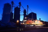 Southbound Union Pacific freight rolls by the grain elevator complex in Beecher, IL during the 'blue hour' just after sunset.