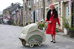 © Licensed to London News Pictures. 13/05/2016. Haworth, UK. A  woman in 1940s costume poses with her pram during the annual 1940's weekend in Haworth, West Yorkshire.  Photo credit : Ian Hinchliffe/LNP