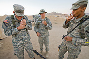 "Curtis Newcomer (left), a soldier at Fort Irwin, California, smokes with one of his counterparts during a break.  (Curtis Newcomer is featured in the book What I Eat: Around the World in 80 Diets.)  He eats his morning and evening meals in a mess hall tent, but his lunch consists of a variety of instant meals in the form of MREs. His least favorite is the cheese and veggie omelet. ""Everybody hates that one. It's horrible,"" he says. A mile behind him, toward the base of the mountains, is Medina Wasl, a fabricated Iraqi village (one of 13 built for training exercises), with hidden video cameras and microphones linked to the base control center for performance reviews.  MODEL RELEASED."