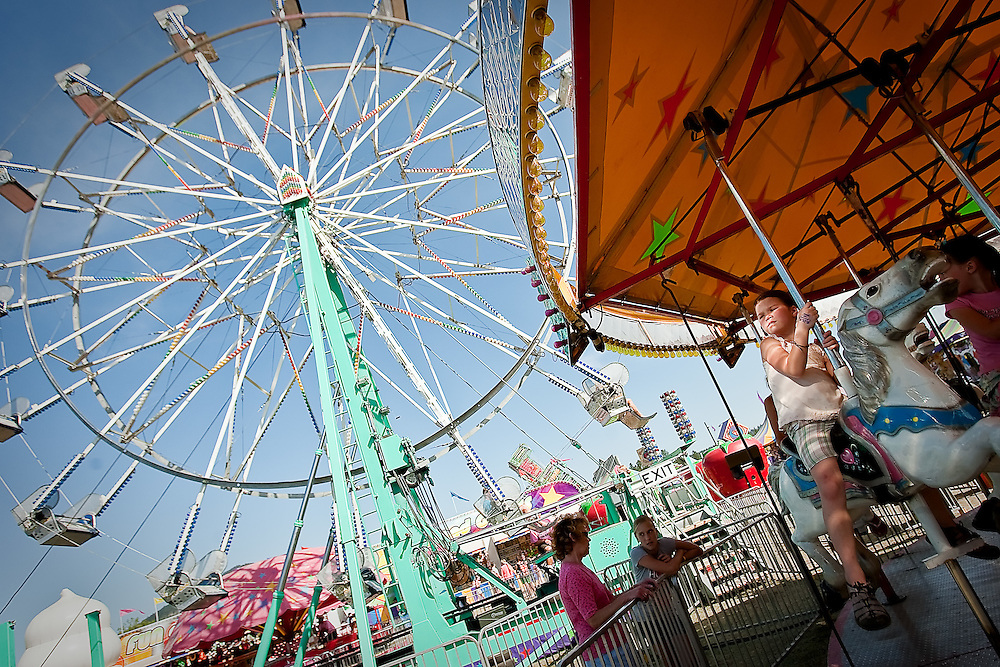 JEROME A. POLLOS/Press..Lauren Baldeck, 6, rides through a sliver of light while on the carousel Friday.