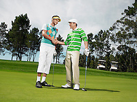 Two male golfers shaking hands on green